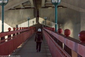 Color picture of a lady walking along the bridge.