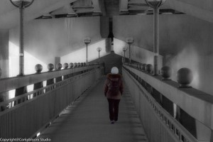 A black and white picture of a lady walking along the bridge.